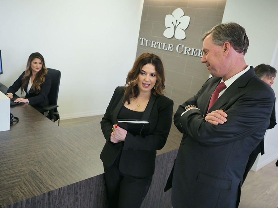 turtle creek dallas office with logo sign in background front desk woman and philip talking and walking