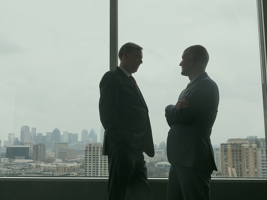 turtle creek dallas two leaders talking professional business men silhouette forms by office building